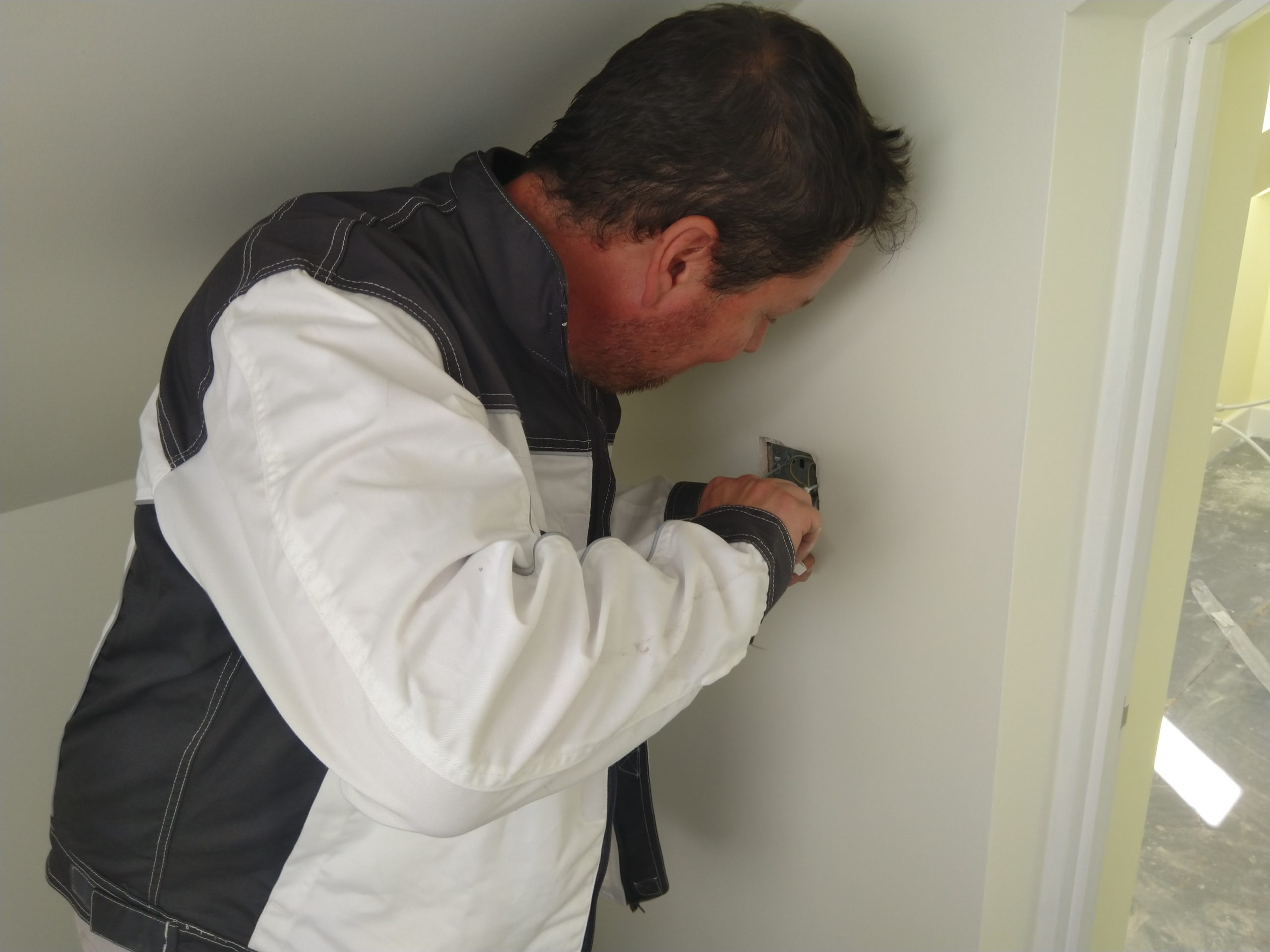 Electrician in Suffolk Working on Light Switch on New Build